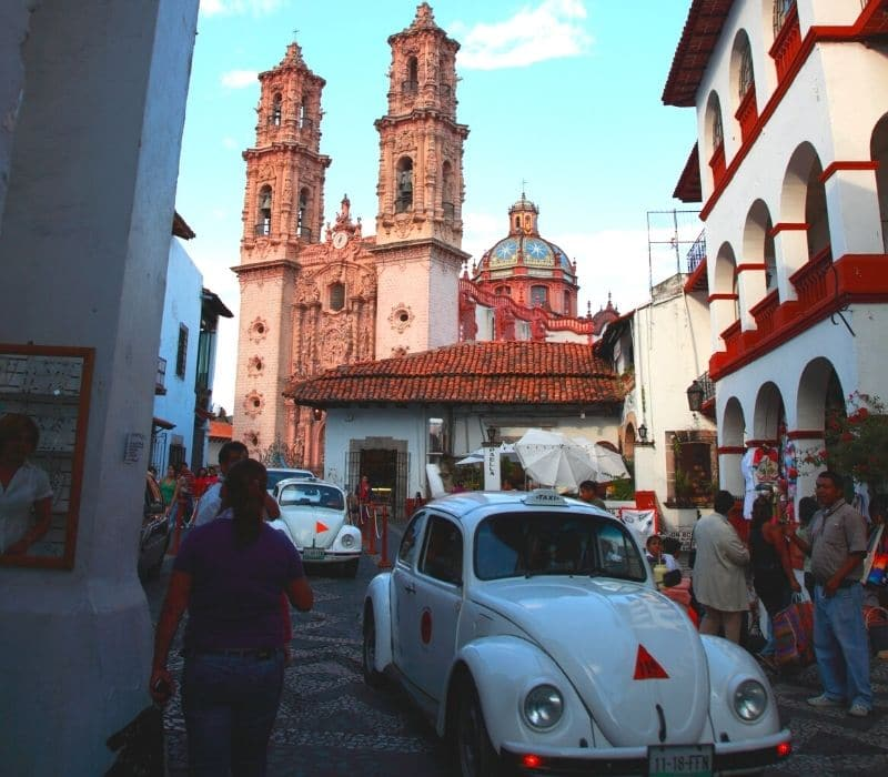 two old white VW Bug cars make their way through the small cobblestone streets of the colonial town of Taxco, one of the most unique places to visit in mexico