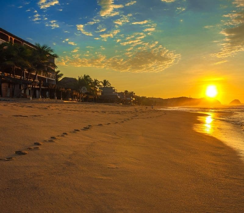 footprints in the sand as the sun sets in zipolite on the coast of oaxaca, one of the Best Mexican Beach Towns