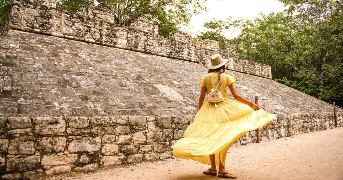 Woman in yellow dress twirling around at Coba, the Best Mayan Ruins in the Yucatan, located in Tulum, Mexico