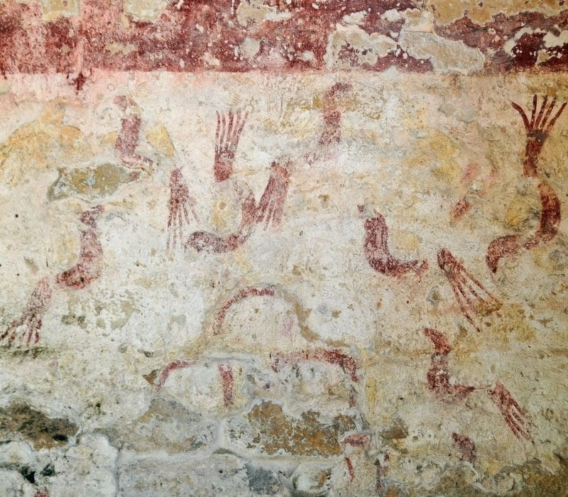 red hand prints pained on the wall at Xel Ha Mayan Ruins in the Yucatan