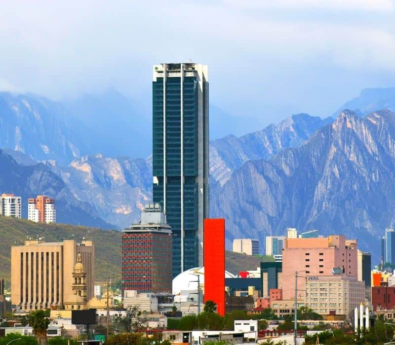 skyscrapers and tall buildings with mountains in the background in Monterrey, one of the safest cities in mexico