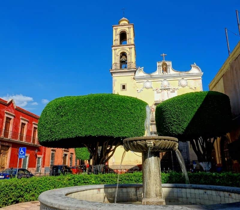 colonial city with manicures trees, stone fountain and spanish style church in queretaro, one of the Safest Cities in Mexico